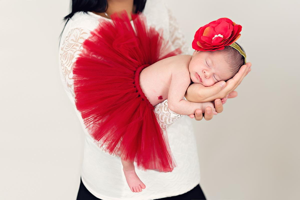 Mutter-haelt-neugeborenes-Baby-in-den-Armen-beim-neugeborenen-Fotoshooting-im-Donna-Bellini-Fotostudio-in-Muenchen