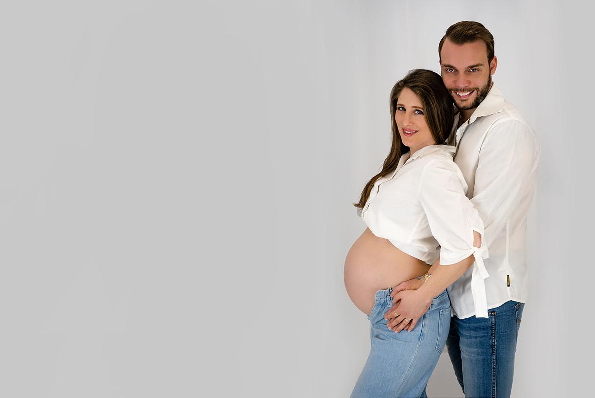 Schwangere Frau in Weiss mit ihrem Mann posieren fuer Babybauch Fotos Donna Bellini Fotostudio fuer Babybauch Fotoshooting