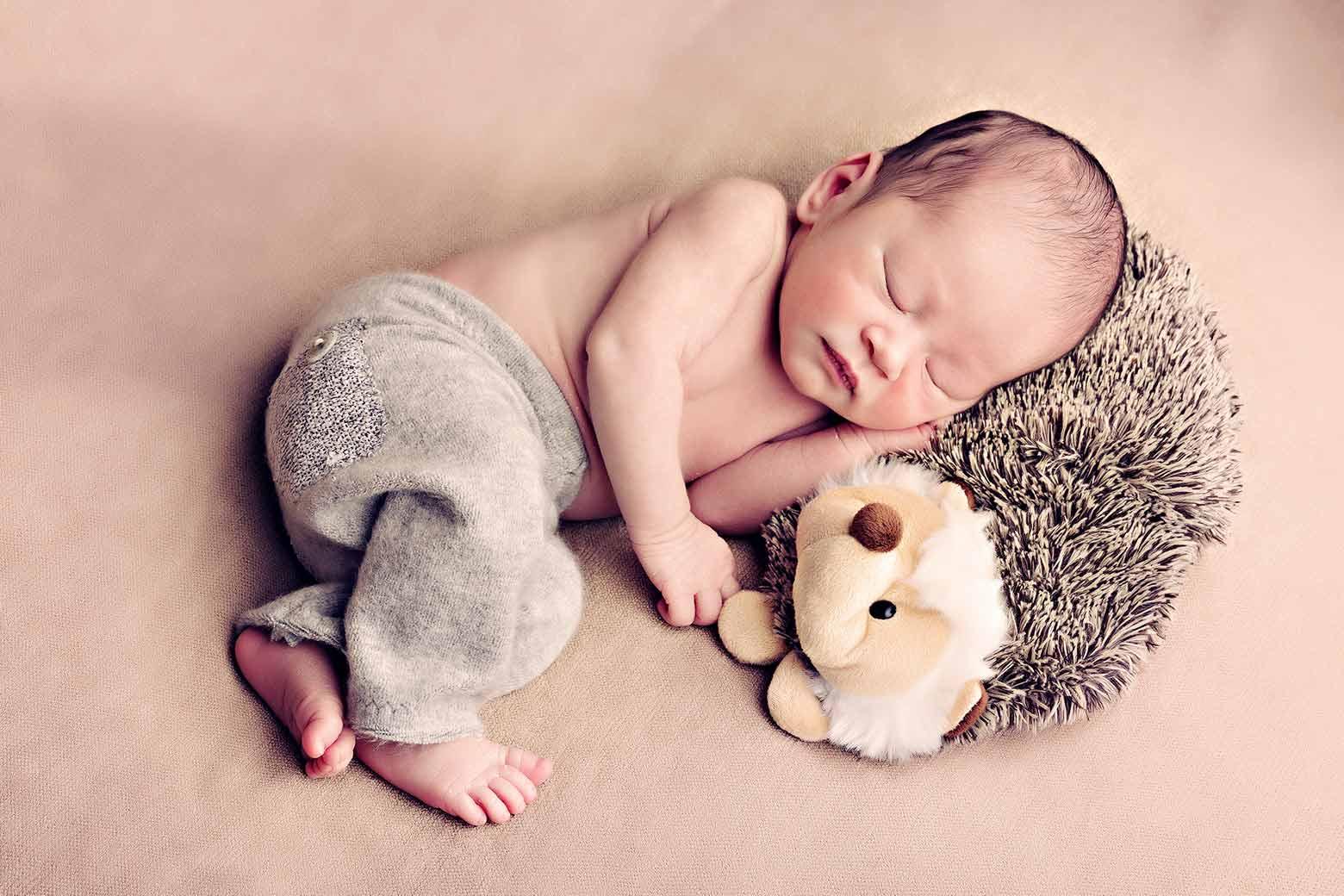 Neugeborenes zusammen mit seinem Spielzeug schlafen Babyfotos